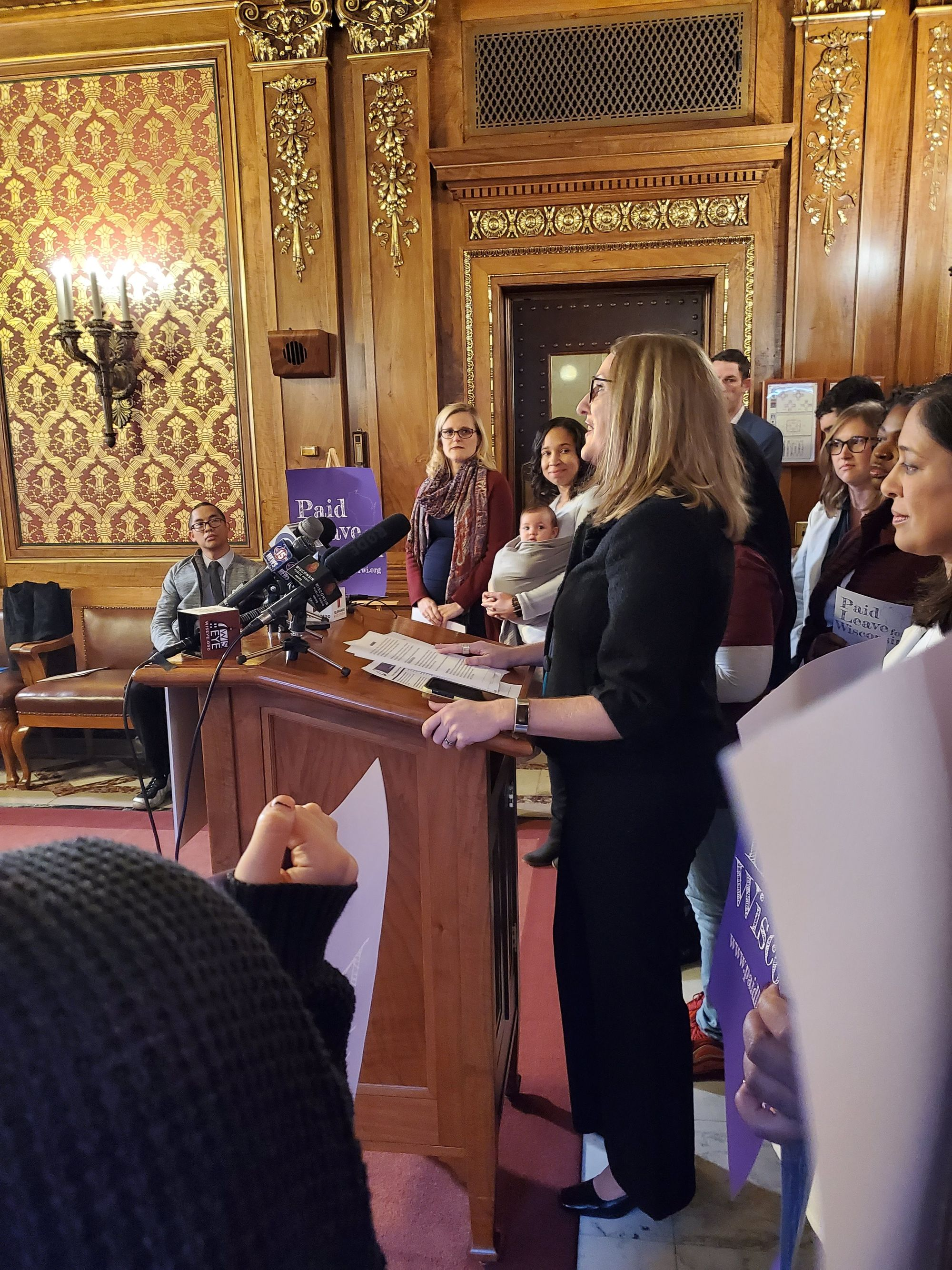 Image of a light skinned woman with light brown hair and dark glasses speaking at a wood podium. There are a variety of people standing around her, some with purple signs that say Paid Leave Wisconsin.       .